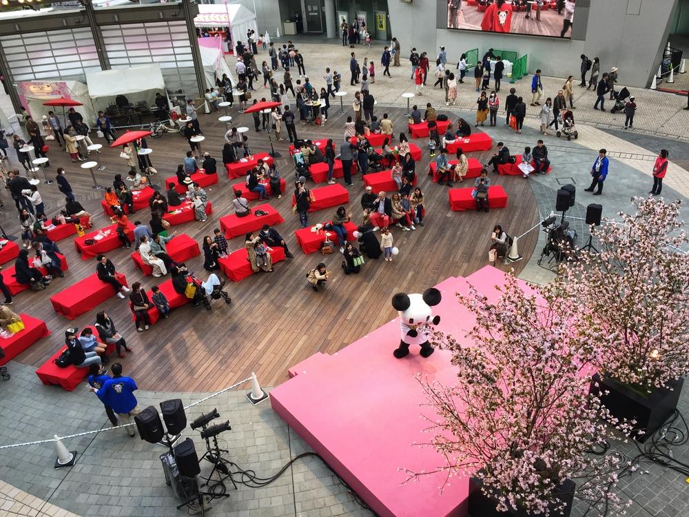 特設ステージでは、テレビ朝日(5ch)のマスコットキャラクター「ゴーちゃん」が桜をバックに熱演中。外国からの観光客と思しき方も一緒に笑顔で写真に収まっていた。